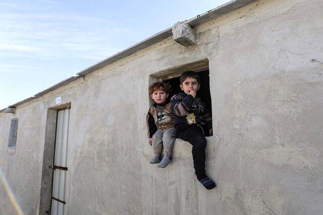 تصویری_از_کودکانی_که_در_لبه_پنجره_یکی_از_اتاقکهای_کمپی_نشستهاند